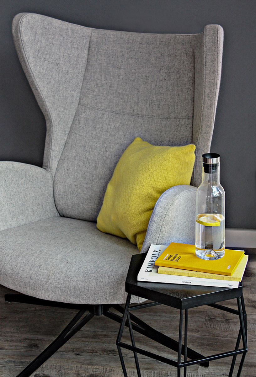 Gray armchair with side table and yellow accessories in the Designsetter flat