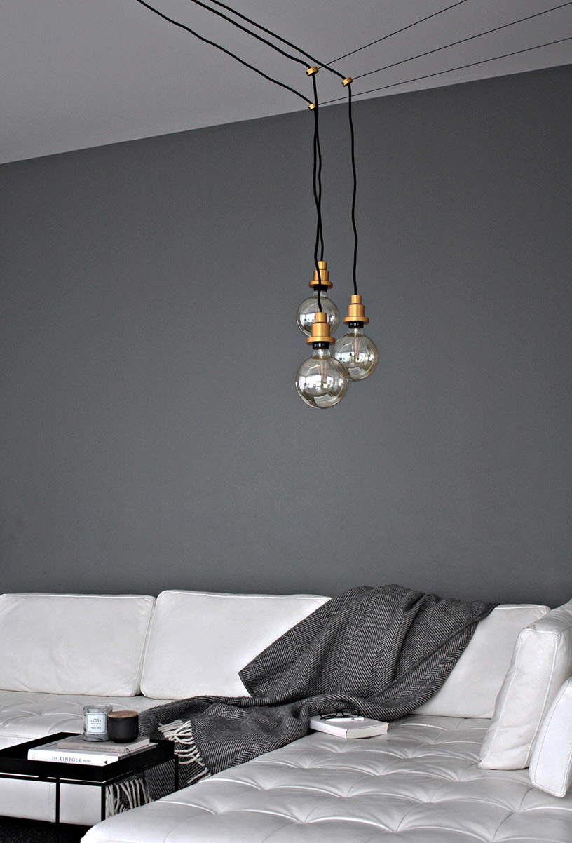 Lamps with a brass cap hanging over a light gray sofa in the Designsetter flat