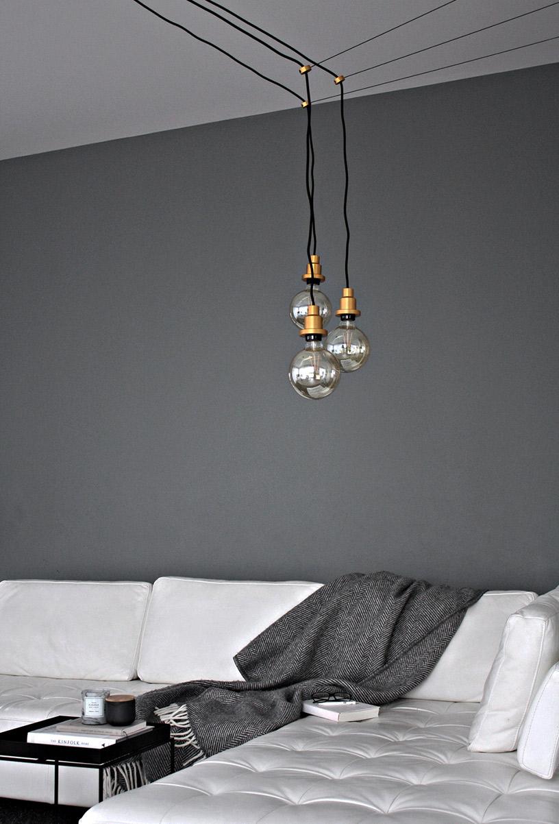 Lampen mit Messing-Fassung hängen über hellgrauem Sofa in der Designsetter-Wohnung