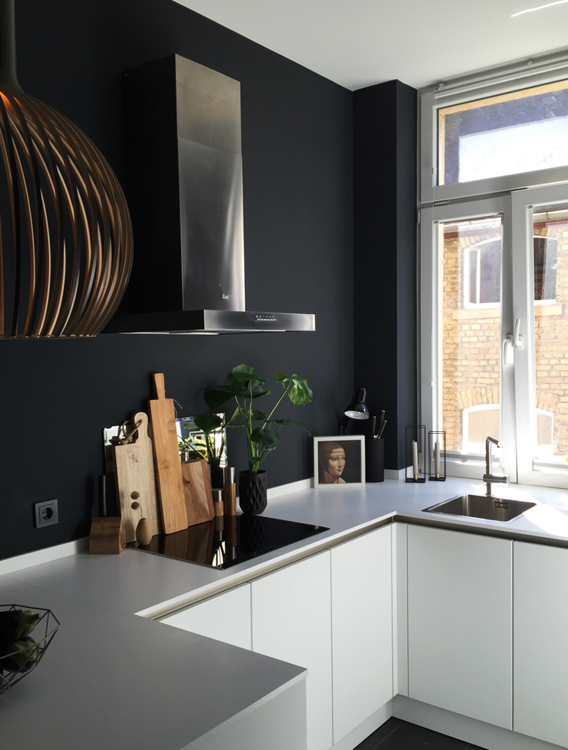Black kitchen wall creates a dramatic backdrop
