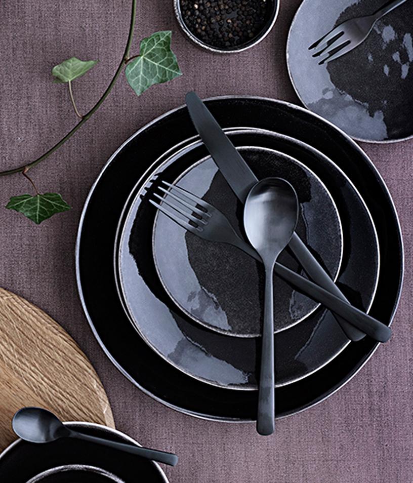 "Black design cutlery ""Hune"" from Broste Copenhagen, arranged atop black tableware"