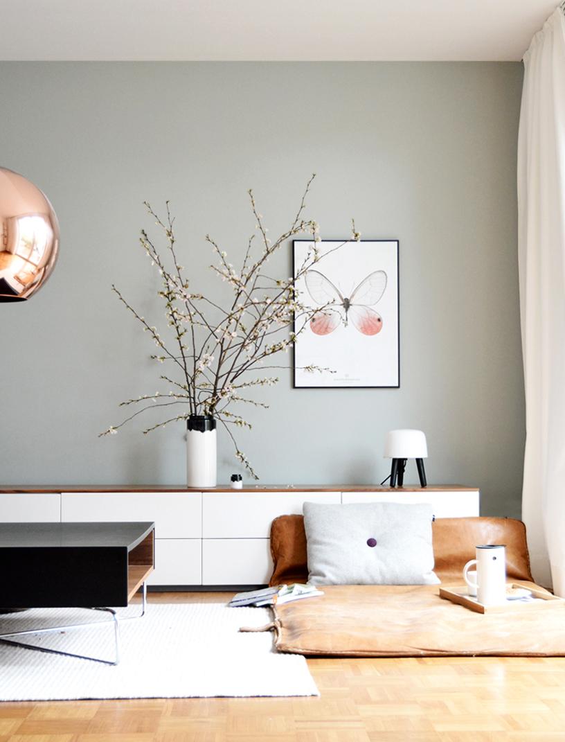 Die hellgraue Wand eines Wohnzimmers schafft einen sanften Übergang zu Decke und Boden