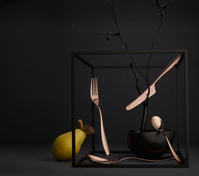 Galvanized Julie Dark Rose cutlery from Hardanger Bestikk, artistically arranged in front of a black background