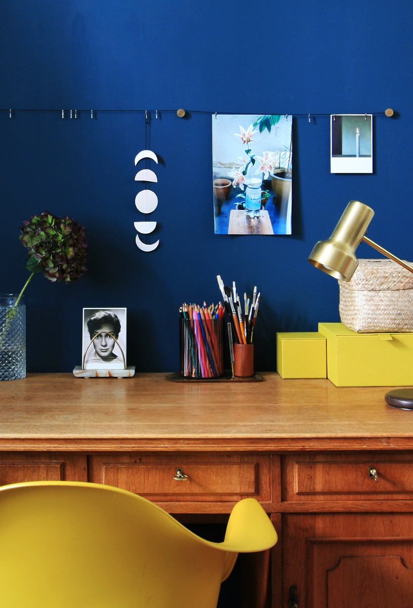 A dark blue wall color creates a cozy atmosphere in this study