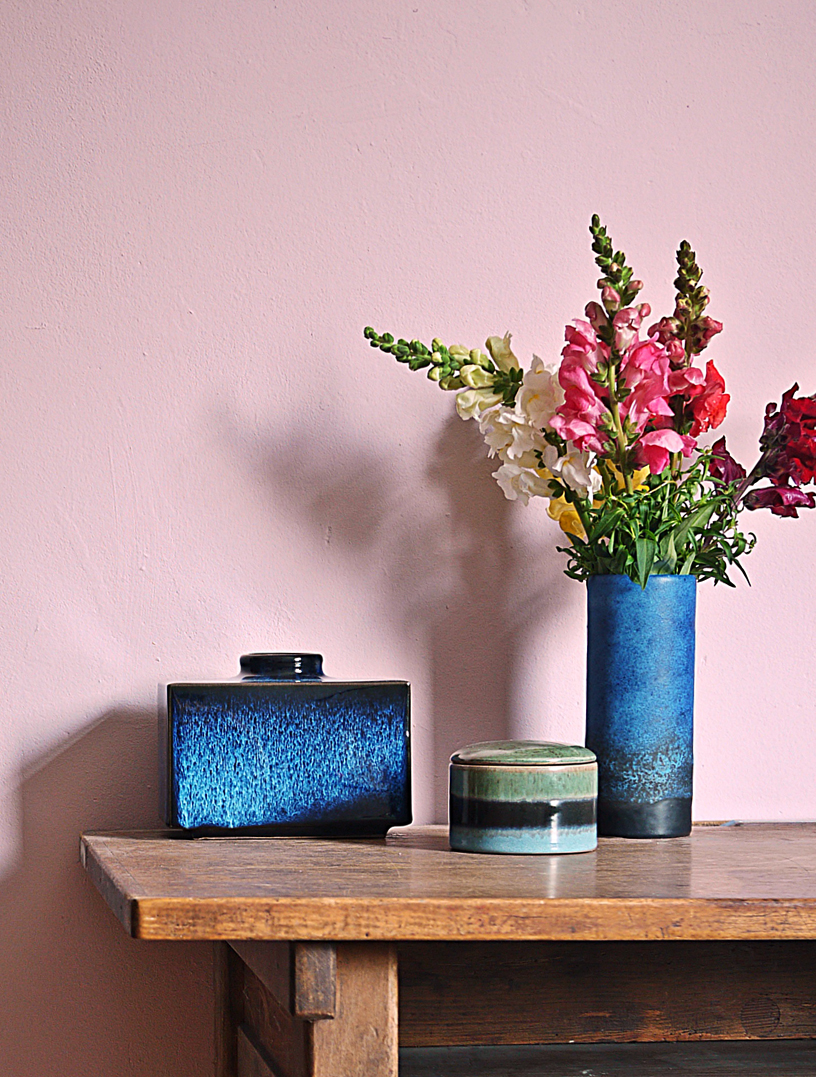 Rose wall color contrasting with dark blue décor objects