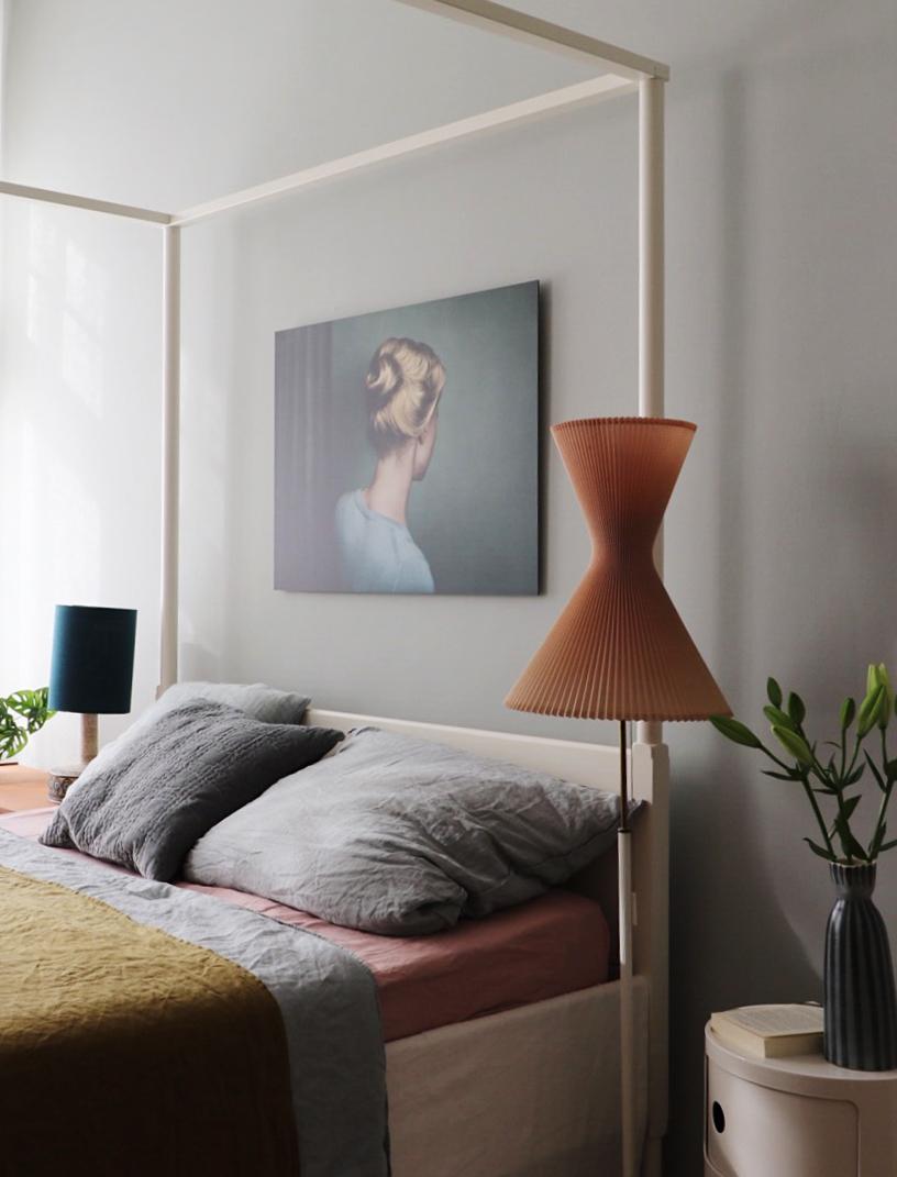 Eine hellgraue Wand sorgt für eine gute Lichtstimmung im Schlafzimmer