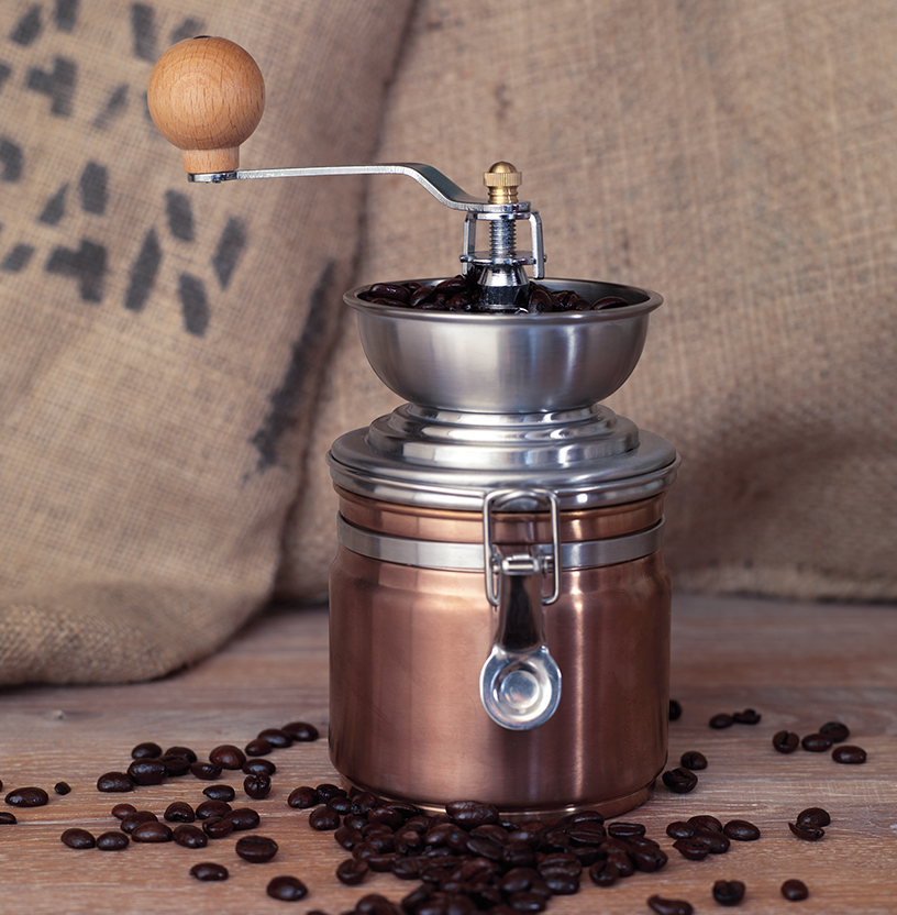 "Copper-colored ""La Cafetiere Origins"" coffee grinder from Creative Tops, artistically arranged in front of a coffee bag amidst coffee beans"