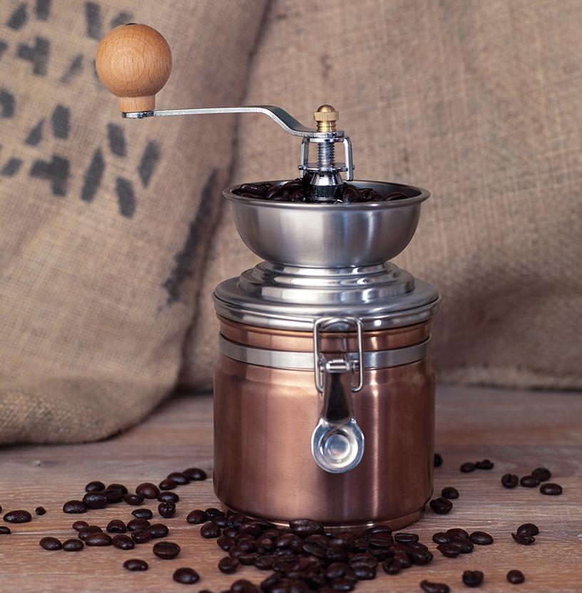 """Kupferfarbene """"La Cafetiere Origins"""" Kaffeemühle von Creative Tops, kunstvoll in Szene gesetzt vor Kaffee-Säcken und Kaffeebohnen"""