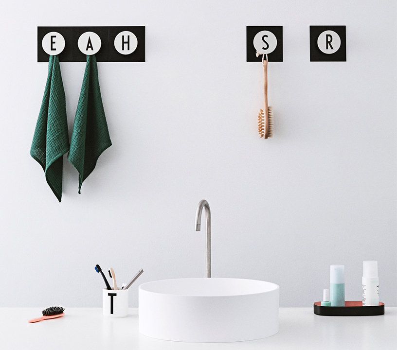 "Bathroom accessories for personal hygiene hanging down from ""Hook2 A-Z"", the wall hook with black and white initials from Design Letters"