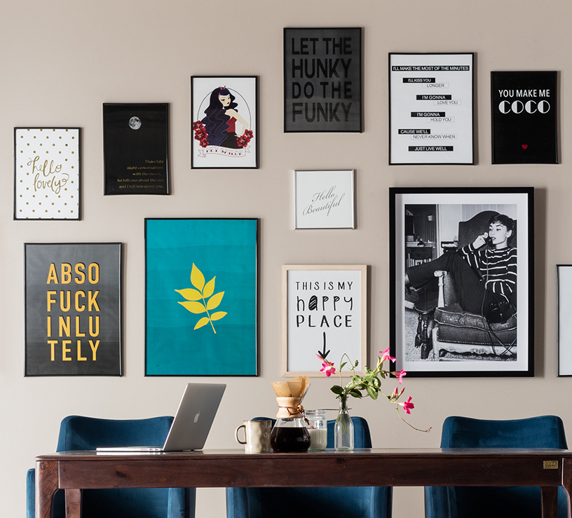Various typography prints from KARE Design decorating a living room wall