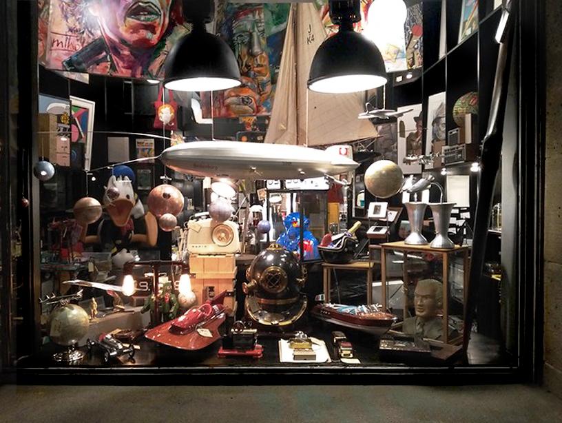 Aussenansicht in das Schaufenster von Last Century Modern, in dem man viele Sammlerstücke und Kunst sieht
