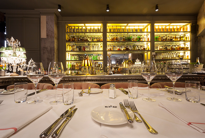 Gedeckter Tisch und kunstvoll beleuchtete Bar des Mon Amie Maxi in Frankfurt