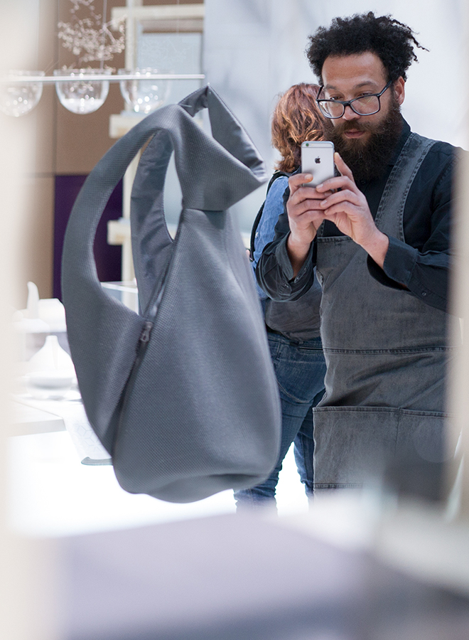 Man taking a photograph of backpack by Inzu at the trend presentation Technological Emotions at Ambiente 2018