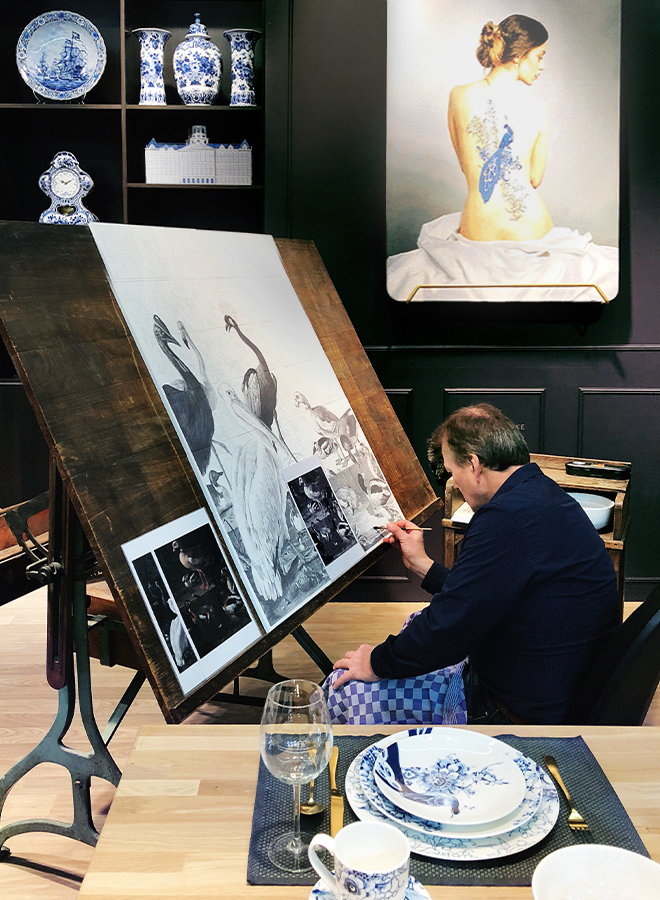 Man working on drawings for painting porcelain tableware for Royal Delft at Ambiente 2018