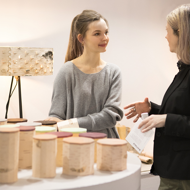Women is showing a lamp and containers made of birch bark to a fair visitor in the Talents area at Ambiente 2018