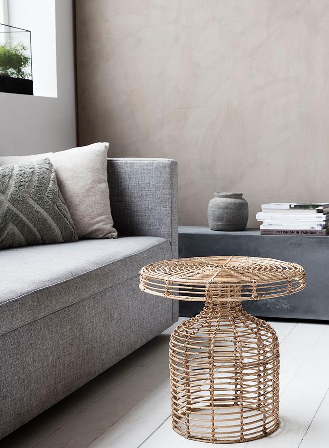 Filigraner und moderner Beistelltisch aus Rattan von House Doctor steht in Wohnzimmer