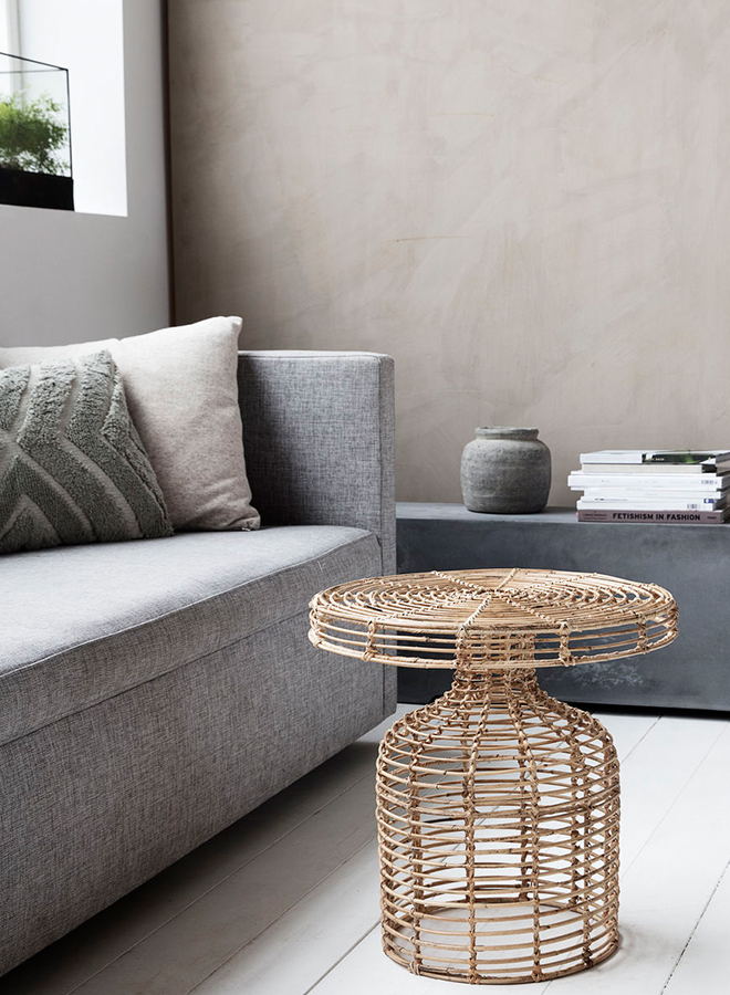 Delicate and modern rattan side table from House Doctor standing in living room
