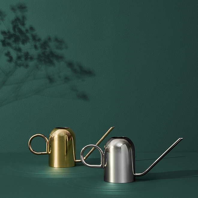 A cooper watering can in silver in the front and a golden cooper watering can in the back by AYTM