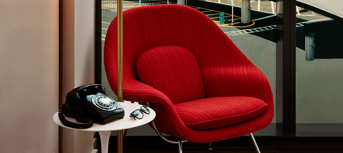 Ein roter Plüschsessel und ein schwarzes Telefon im Retrolook in einem Hotelzimmer